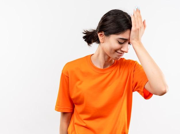 Jong meisje dat oranje t-shirt draagt dat met hand op haar hoofd voor fout kijkt die zich over witte muur bevindt