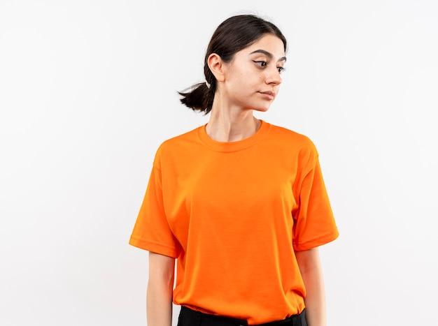 Jong meisje dat oranje t-shirt draagt dat opzij met droevige uitdrukking kijkt die zich over witte muur bevindt