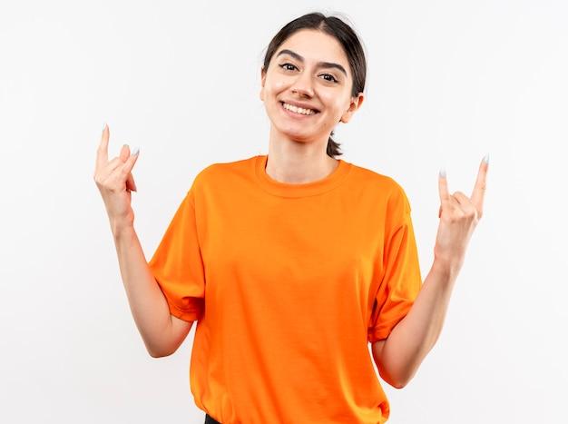 Jong meisje dat oranje t-shirt draagt dat rotssymbool toont dat met gelukkig gezicht glimlacht dat zich over witte muur bevindt