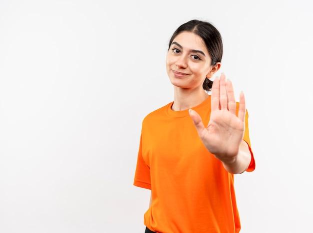 Jong meisje dat oranje t-shirt draagt dat stopgebaar met hand met glimlach op gezicht maakt dat zich over witte muur bevindt