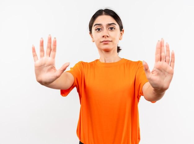 Jong meisje dat oranje t-shirt draagt dat stopgebaar met handen met ernstig gezicht maakt dat zich over witte muur bevindt