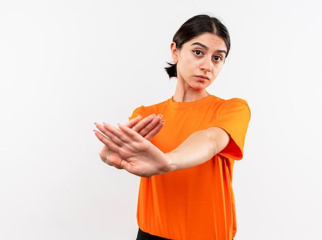 Jong meisje dat oranje t-shirt draagt dat stopteken kruist wapens met ernstig gezicht dat zich over witte muur bevindt