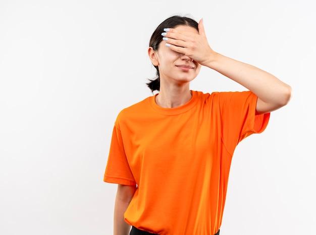 Jong meisje dat oranje t-shirt draagt die ogen bedekt met hand het glimlachen status over witte muur