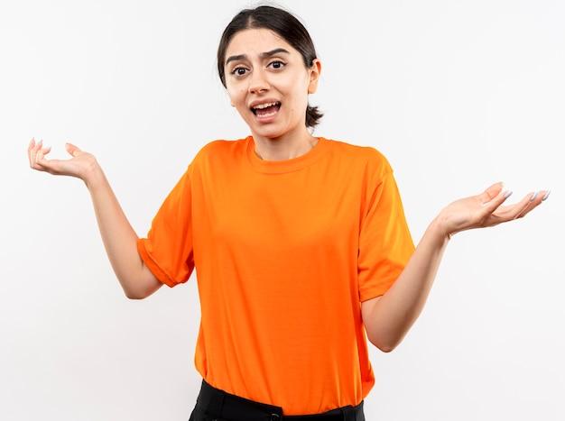 Jong meisje dat oranje t-shirt draagt verward schouderophalend schouders die geen antwoord hebben die zich over witte muur bevinden