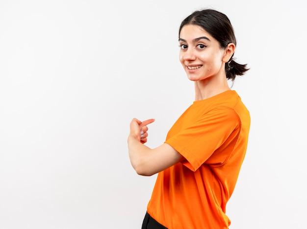 Jong meisje dat oranje t-shirt met glimlach op gezicht draagt dat met vinger terug richt die zich over witte muur bevindt