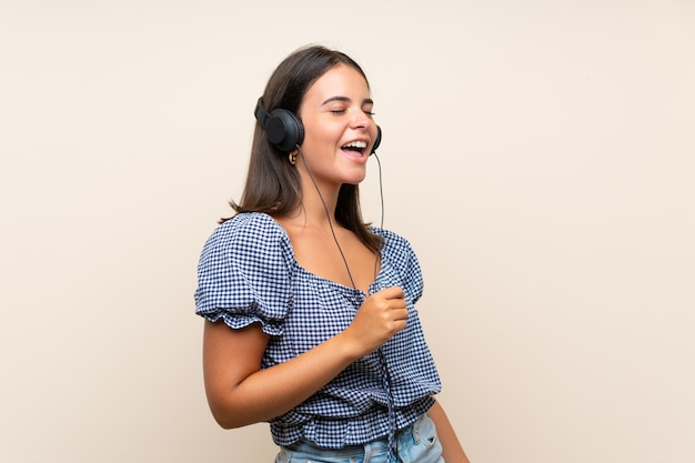 Jong meisje dat over geïsoleerde muur aan muziek met hoofdtelefoons luistert