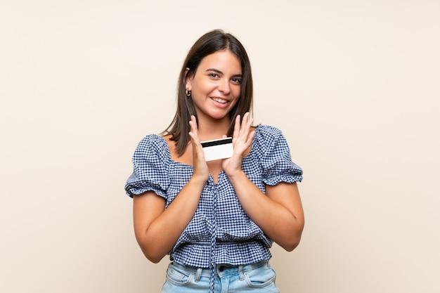 Jong meisje dat over geïsoleerde muur een creditcard houdt