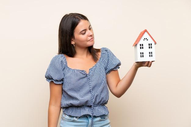 Jong meisje dat over geïsoleerde muur een klein huis houdt