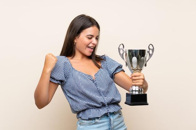 Jong meisje dat over geïsoleerde muur een trofee houdt