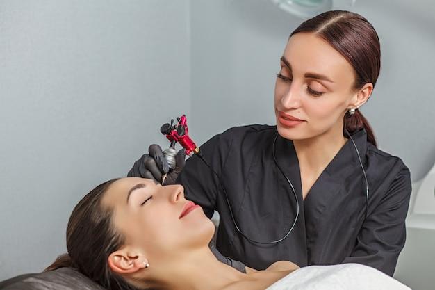 Jong meisje dat permanente eyeliner in schoonheidsstudio toepast