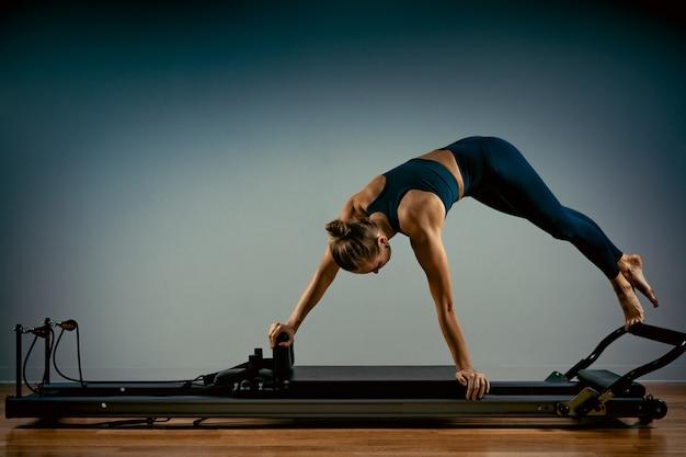 Jong meisje dat pilates oefeningen met een hervormerbed doet. mooie slanke fitnesstrainer op hervormer grijze achtergrond, low key, kunstlicht. fitness concept