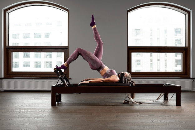 Jong meisje dat pilatesoefeningen doet met een hervormerbed. mooie slanke fitnesstrainer op hervormer grijze achtergrond, low key, kunstlicht. geschiktheidsconcept.