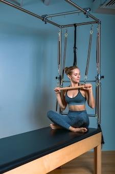Jong meisje dat pilatesoefeningen met een hervormerbed doet. mooie slanke fitnesstrainer op de grijze muur van de hervormer, rustig, kunstlicht. fitness concept.