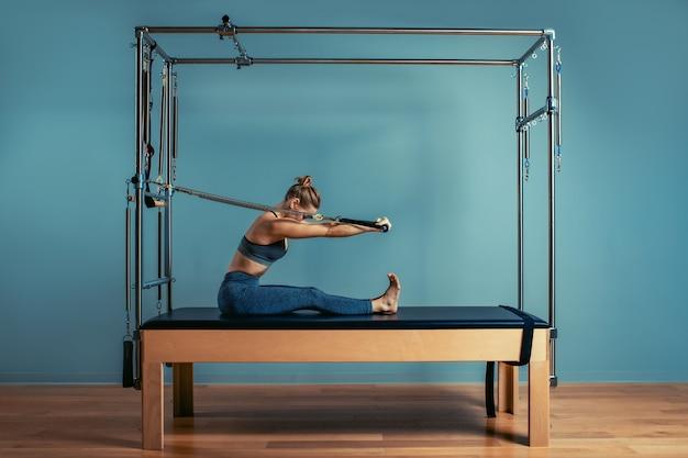 Jong meisje dat pilatesoefeningen met een hervormerbed doet. mooie slanke geschiktheidstrainer op hervormer grijze achtergrond, rustig, kunstlicht. fitness concept