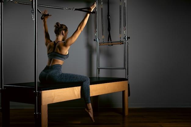 Jong meisje dat pilatesoefeningen met een hervormerbed doet