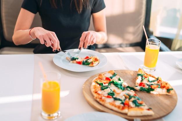 Jong meisje dat pizza in een restaurant eet.