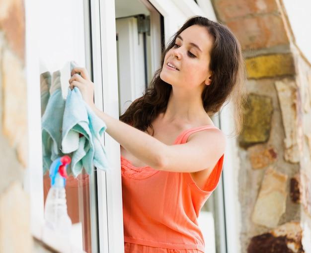 Jong meisje dat plastic vensters met spuitbus wast