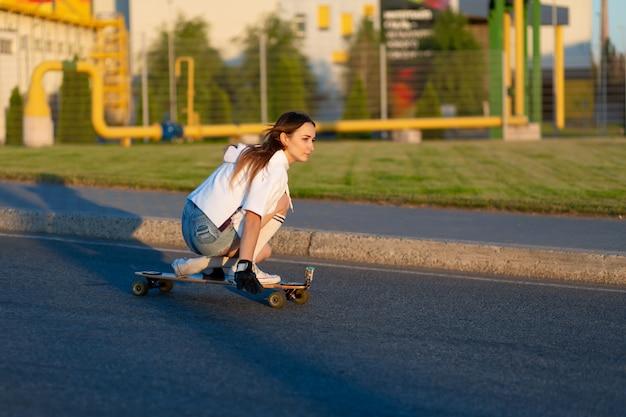 Jong meisje dat pret met skateboard op de weg heeft. jonge vrouw die op een zonnige dag schaatst