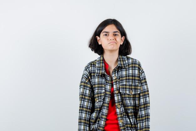 Jong meisje dat rechtop staat en voor de camera poseert in een geruit overhemd en een rood t-shirt en er somber uitziet. vooraanzicht.