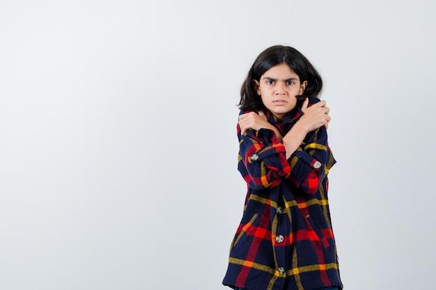 Jong meisje dat rilt van de kou in een geruit overhemd en er boos uitziet, vooraanzicht.