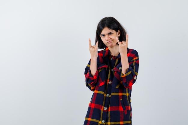 Jong meisje dat rock-'n-roll-gebaren in geruit overhemd toont en er schattig uitziet. vooraanzicht.
