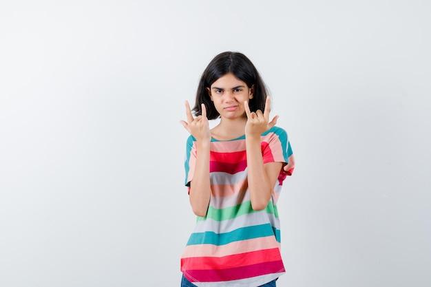 Jong meisje dat rock n roll-gebaren toont in een kleurrijk gestreept t-shirt en er zelfverzekerd uitziet. vooraanzicht.