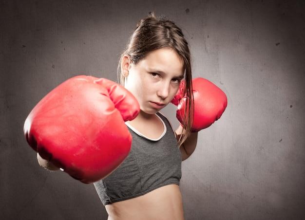 Jong meisje dat rode bokshandschoenen draagt