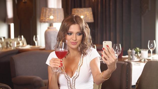 Jong meisje dat rode wijn in restaurant drinkt.