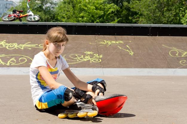 Jong meisje dat rollerblades draagt die bij het skatepark ontspannen