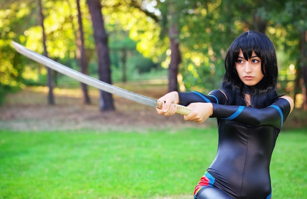 Jong meisje dat samoeraienzwaard houdt. origineel cosplay-personage