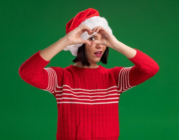 Jong meisje dat santahoed draagt die camera bekijkt die hartteken voor oog doet dat op groene achtergrond wordt geïsoleerd