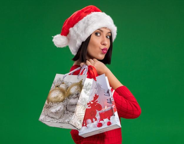 Jong meisje dat santahoed draagt die zich in profielmening bevindt die de zakken van de kerstmisgift op schouder met samengeknepen lippen houdt die op groene muur worden geïsoleerd