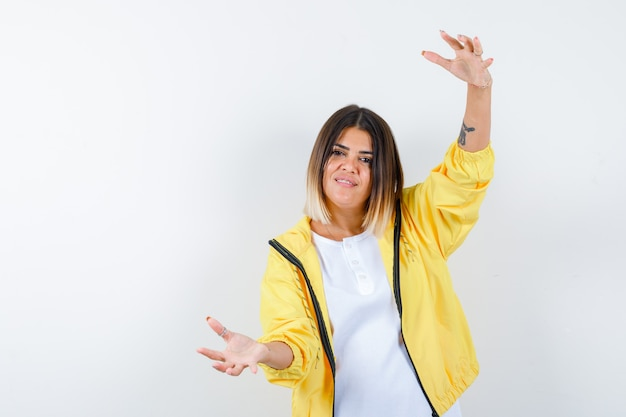 Jong meisje dat schalen in wit t-shirt, geel jasje toont en zelfverzekerd, vooraanzicht kijkt.