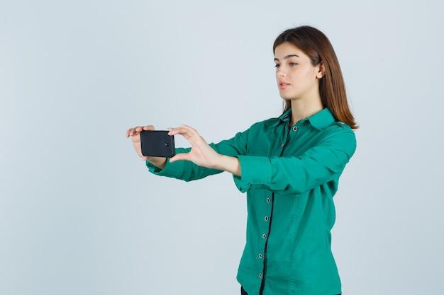 Jong meisje dat selfie in groene blouse, zwarte broek neemt en gericht kijkt. vooraanzicht.