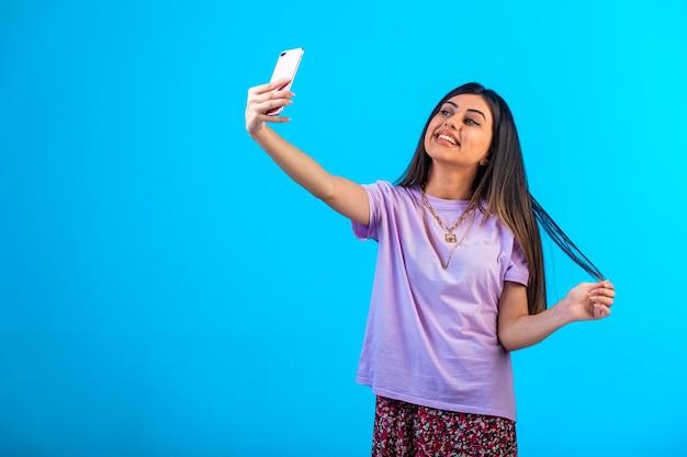 Jong meisje dat selfie op haar telefoon neemt.