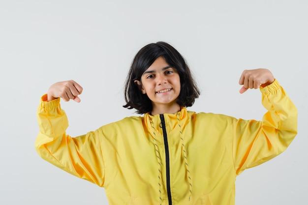 Jong meisje dat spieren in geel bomberjack toont en gelukkig kijkt.