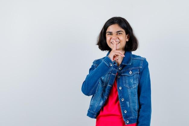 Jong meisje dat stiltegebaar in rood t-shirt en jeansjasje toont en gelukkig kijkt