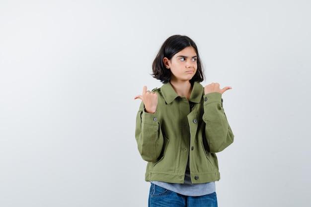Jong meisje dat tegengestelde richtingen wijst, wegkijkt in grijze trui, kaki jas, jeansbroek en serieus kijkt, vooraanzicht.