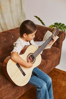 Jong meisje dat thuis gitaar leert spelen