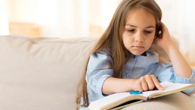 Jong meisje dat thuis met exemplaarruimte bestudeert