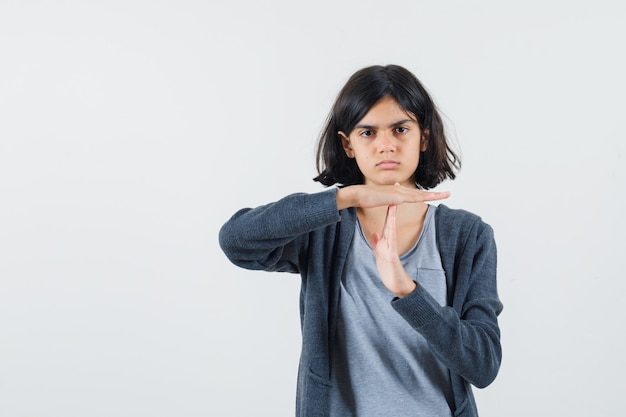 Jong meisje dat tijdpauze in lichtgrijs t-shirt en donkergrijze hoodie met ritssluiting toont en er schattig uitziet.