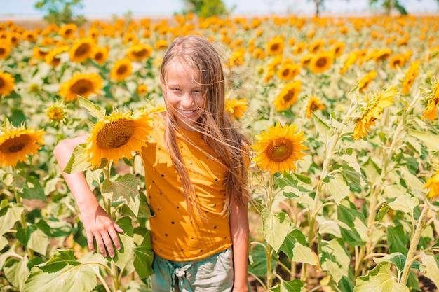 Jong meisje dat van aard op het gebied van zonnebloemen geniet.