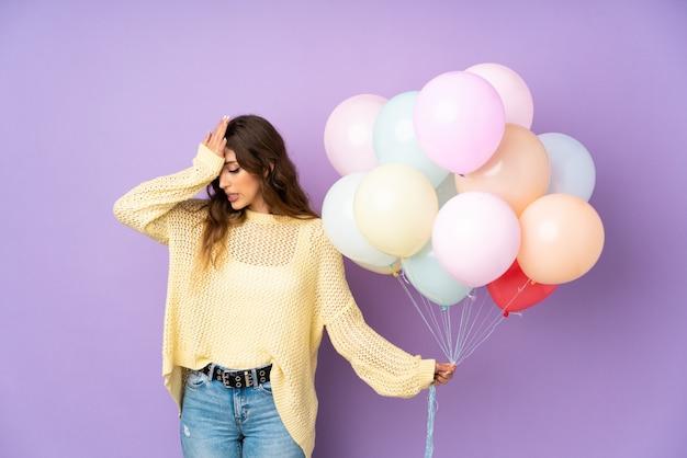 Jong meisje dat veel ballons over muur houdt
