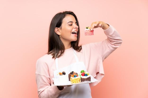 Jong meisje dat veel verschillende minicakes over geïsoleerde muur houdt