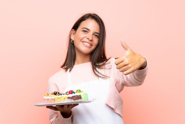 Jong meisje dat veel verschillende minicakes over geïsoleerde muur met omhoog duimen houdt omdat er iets goeds is gebeurd