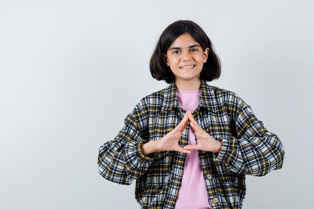 Jong meisje dat verzekeringsgebaar in geruit overhemd en roze t-shirt toont en er schattig uitziet, vooraanzicht.