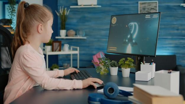 Jong meisje dat videogames speelt op de computer na online school