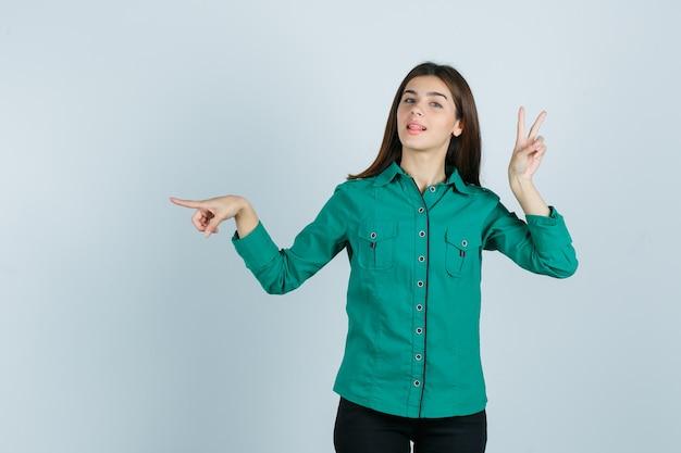 Jong meisje dat vredesgebaar toont, naar links wijst met wijsvinger in groene blouse, zwarte broek en er zelfverzekerd uitziet. vooraanzicht.