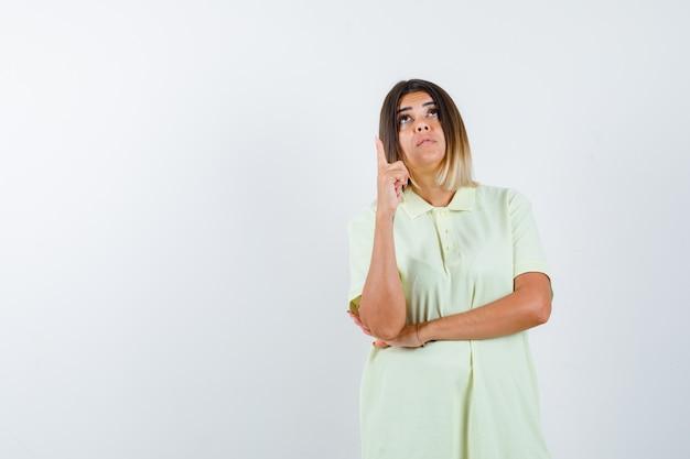 Jong meisje dat wijsvinger in eureka-gebaar in t-shirt opheft en peinzend, vooraanzicht kijkt.