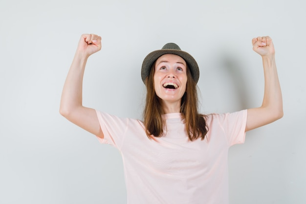 Jong meisje dat winnaargebaar in roze t-shirt, hoed toont en gelukkig kijkt. vooraanzicht.